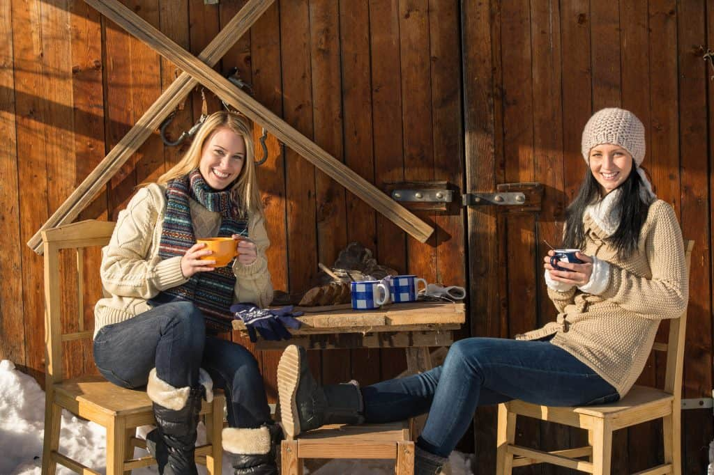 Two young women enjoy tea winter cottage